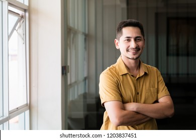Young man asian smiling and looking at camera. Portrait of a happy handsome young man in office. Close up face of young cool trendy man looking at camera