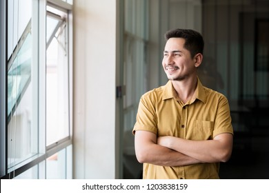 Young man asian smiling. Portrait of a happy handsome young man in office. Close up face of young cool trendy man looking outside.