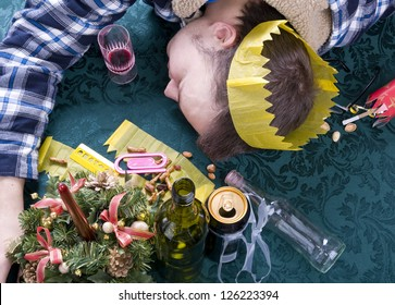 young man asleep with head on table after party