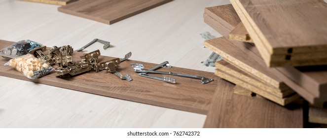 young man assembles furniture in the new house, the details laid out around him on the floor