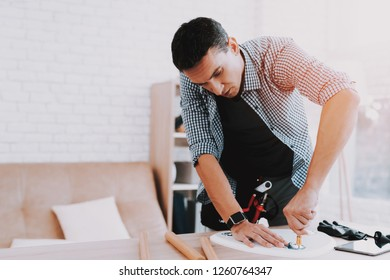 Young Man Assembling Coffee Table and Stools. Furniture Fittings. Engineer with Tool. Young Man at Home. Wooden Coffee Table. Selfmade Furniture. Man and Hobby. White Table in Room.