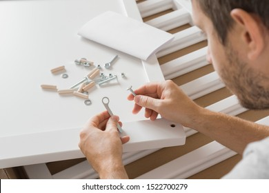 Young man assembling new furniture. Father preparation for future baby. White wooden planks for crib. Hands holding wrench and screw.