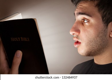 Young man astonished and intrigued by open Bible