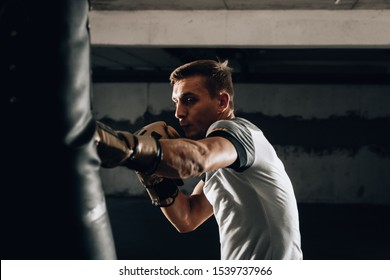 Young man athlete boxing workout in fitness gym on dark background.Athletic man training hard.Kick boxing concept