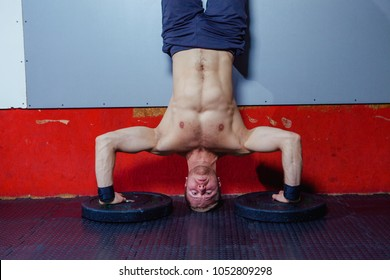 Young Man Athlete Doing Extreme Pushups Handstand As Part Of Bodybuilding Training