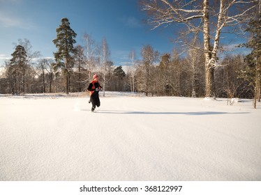 Young man athlete running off road in beautiful snowy forest.