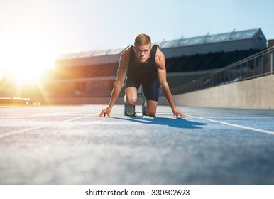 Young man athlete in starting position ready to start a race. Male sprinter ready for a run on racetrack looking at camera with sun flare.