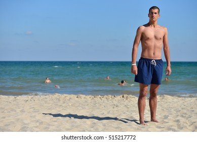 Young man with athletic body in blue shorts standing with his back at the sea. Vacation concept