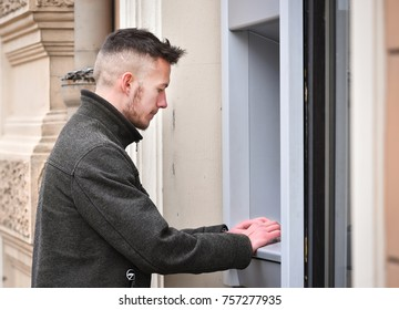 young man at atm in winter