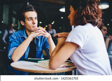 Young man attentively listening lovely girlfriend during date in modern cafe interior.Hipster guys communicating with each other and discussing common startup during friendly meeting in coffee shop