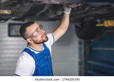 A young man auto mechanic in overalls at his workplace repairs the car's suspension, shines a lantern on the chassis. Concept Worker at an automobile repair shop, a car lifted on a lift