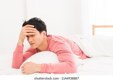 The young man was awakened by the morning alarm clock while on the bed.Shallow depth of field.unhappy from noisy sound of alarm clock and trying to turn it off. Hangover,lazy and sleepless concept.