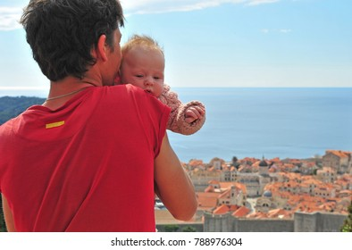 Young man with a baby looking at Dubrovnik old town from above