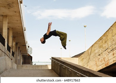 Young man back flip. Parkour in the urban space. Sport in the city. Sport Activities outdoors. Acrobatics