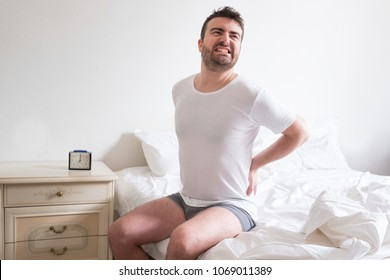 Young man with back pain sitting on bed in his room