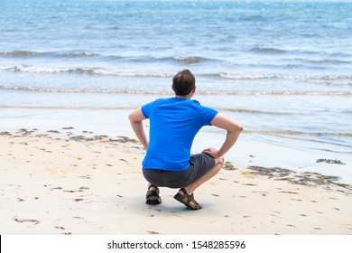 Young man back squatting crouching sitting on beach bay shore sand in Florida near Pensacola