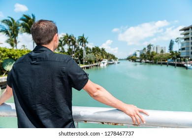 Young man back wearing black shirt standing leaning on bridge railing in Bal Harbour, Miami Florida with green ocean Biscayne Bay