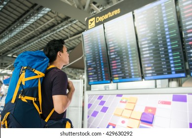 Young man with backpack in airport looking flight timetable