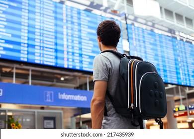 Junge Mann mit Rucksack am Flughafen bei Flugplan