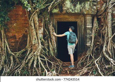Young man with backpack coming to ancient monuments under the giant roots of the tree near Siem Reap (Angkor Wat) in Cambodia