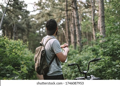 Young man with backpack cycling on a forest path, active lifestyle, playing sports in nature.
