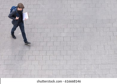 Young man with backpack and headphone going to school college university from above