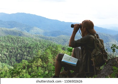Young man with backpack and holding a binoculars sitting on top of mountain