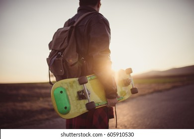 Young man with backpack holding his skateboard, rear view