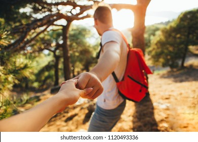 A young man with a backpack leads his girlfriend. Follow me.
