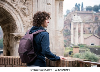 Young man with backpack looking at Roman forum