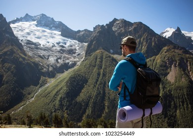 Young man with backpack and mat standing on top of a mountain enjoying the view of mountains. Freedom Lifestyle Adventure Active Vacations