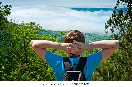 a young man with a backpack in the mountains admiring the view