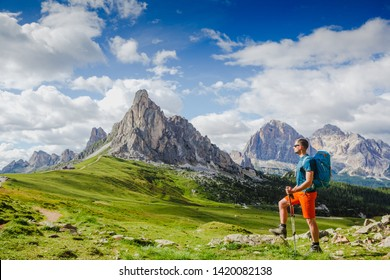 Young man with backpack on a mountain trail, Dolomites Mountains, Italy