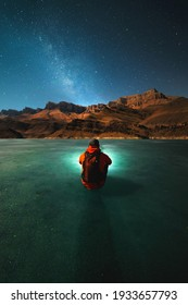 A young man with a backpack sits on the ice of a frozen lake at night in winter and looks at the mountains and the milky way by the light of the moon