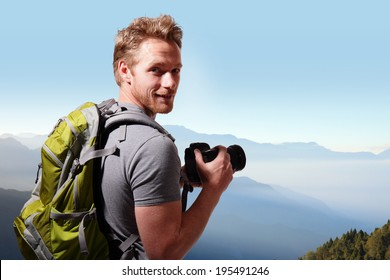 Young man with backpack taking a photo on the top of mountains, caucasian