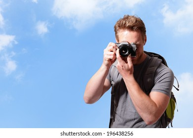 Young man with backpack taking a photo with sky background, caucasian