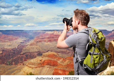 Young man with backpack taking a photo on the top of mountains at Grand Canyon, caucasian