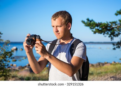 young man with backpack taking a photo on the beach