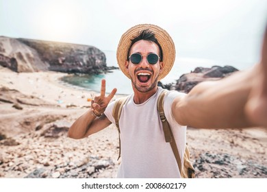 Young man with backpack taking selfie portrait on a mountain - Smiling happy guy enjoying summer holidays at the beach - Millennial showing victory hands symbol to the camera - Youth and journey