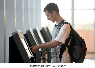 Young man with backpack touching interactive display using self service machine, doing self-check-in for flight or buying airplane tickets at automatic device in modern airport terminal building