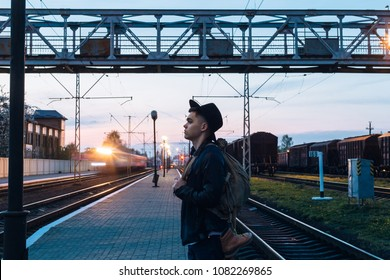 Young man with a backpack at the train station waiting for the train