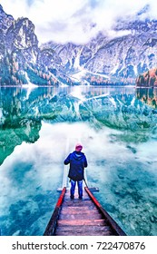 Young man backpacker dressed red hat and blue jacket admiring pristine untouched nature rear view over green water of Lake Braies - lago di Braies and Dolomite alpine mountains in background. Italy.