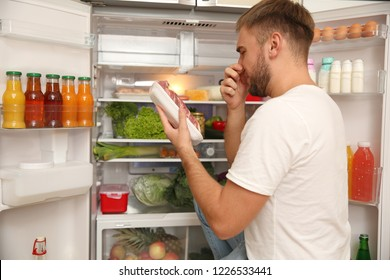 Young man with bad smelling meat near refrigerator in kitchen
