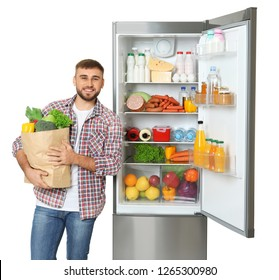 Young man with bag of groceries near open refrigerator on white background