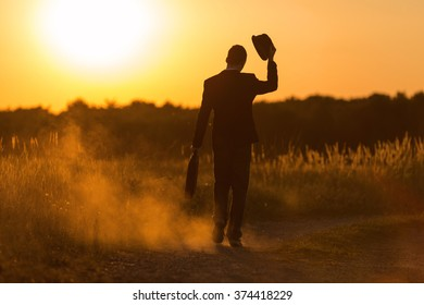 A young man with bag and hat walks into the sunset