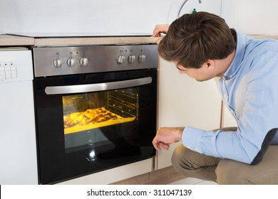 Young Man Baking Bread In Oven Appliance At Home