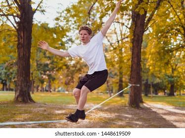 Young man balancing and jumping on slackline. Man walking, jumping and balancing on rope in park.