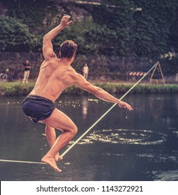 Young man balancing on slackline. Man walking and balancing on rope over water