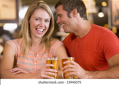 Young man in bar whispering into his girlfriends ear