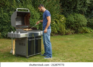 Young man at a barbecue grill